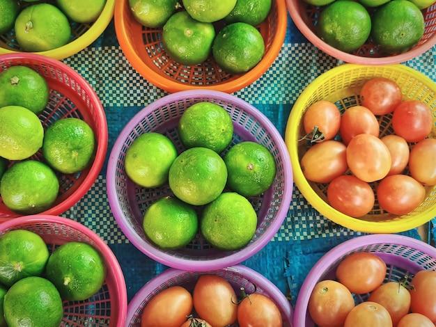 Visão de alto ângulo de limões frescos e pequenos tomates em cestas de plástico