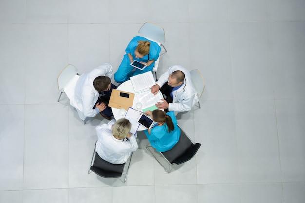 Visão de alto ângulo de médicos e cirurgiões interagindo entre si em reuniões