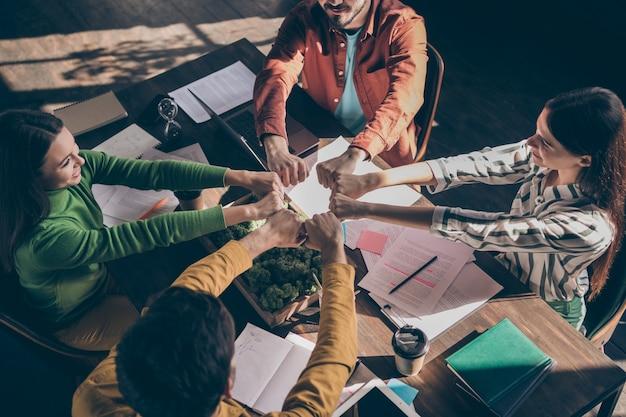 Visão de alto ângulo de pessoas alegres criando uma grande equipe unida para superar as dificuldades de trabalho juntos mostrando os punhos
