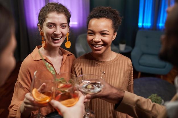 Visão de alto ângulo de um grupo multiétnico de amigos tilintando copos enquanto desfruta de uma festa dentro de casa