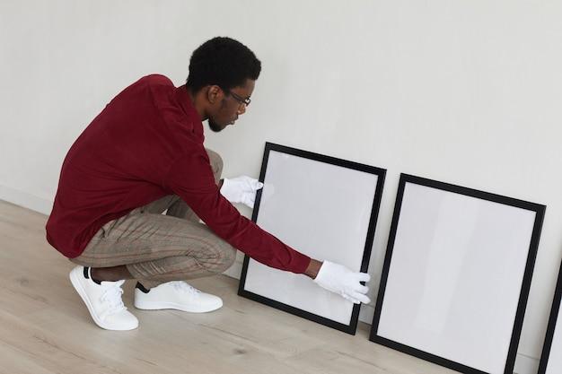 Visão de alto ângulo de um homem afro-americano montando molduras pretas vazias no chão enquanto planeja uma galeria de arte ou exposição.