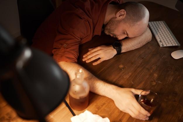 Visão de alto ângulo de um homem maduro dormindo à mesa após beber álcool