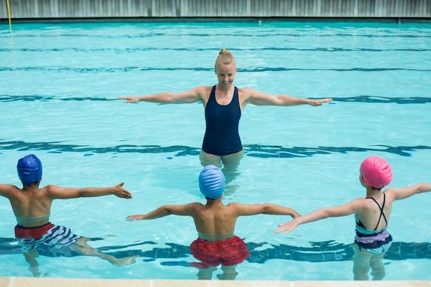 Visão de alto ângulo do instrutor ensinando alunos na piscina