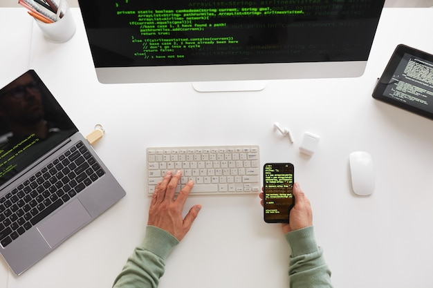 Visão de alto ângulo do programador sentado à mesa usando computador, laptop e design de site de programação de celular