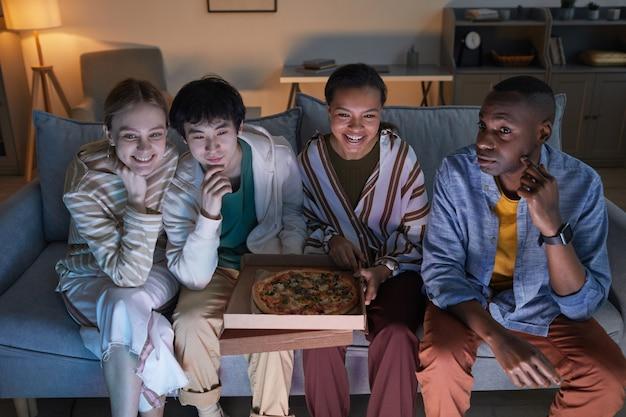 Visão de alto ângulo em um grupo diversificado de amigos assistindo tv em casa iluminada por uma luz azul e sorrindo