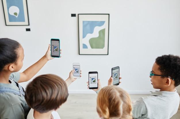 Visão de alto ângulo em um grupo diversificado de crianças segurando smartphones na galeria de arte e tirando fotos de pinturas, mundo digital, espaço de cópia