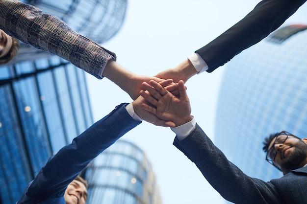 Visão de baixo ângulo da equipe de negócios de mãos dadas, se unindo e apoiando uns aos outros na cidade