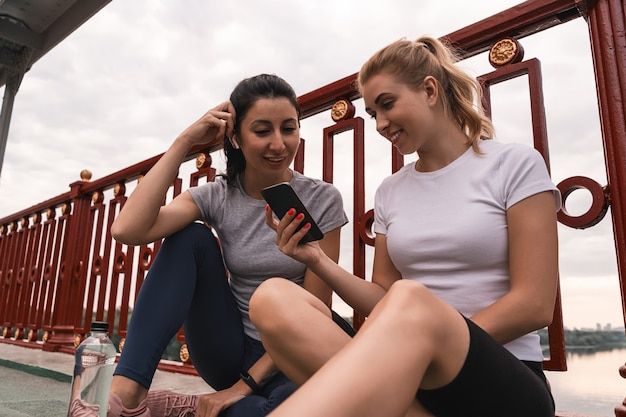 Visão de baixo ângulo de mulheres bonitas felizes em roupas esportivas, sentadas na rua enquanto usam o smartphone e lêem a mensagem