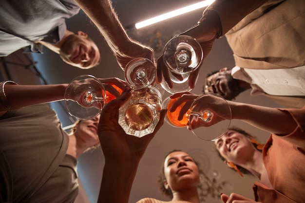 Visão de baixo ângulo de um grupo multiétnico de amigos tilintando copos enquanto desfruta de uma festa dentro de casa