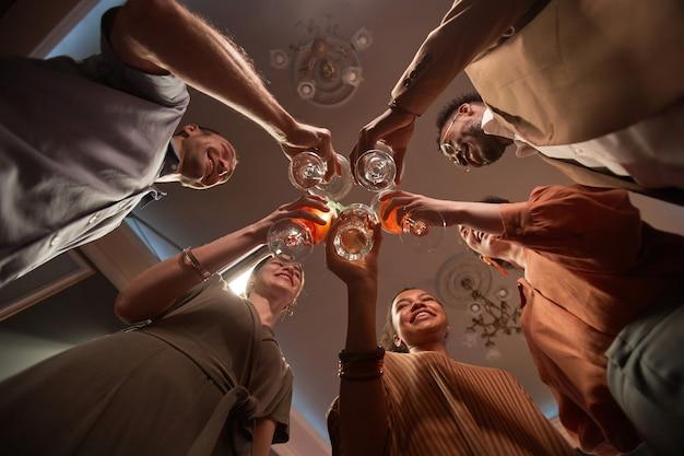 Visão de baixo ângulo de um grupo multiétnico de pessoas tilintando copos enquanto desfruta de uma festa dentro de casa