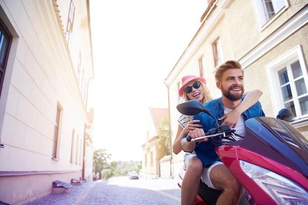 Visão de baixo ângulo do casal em uma scooter rápida