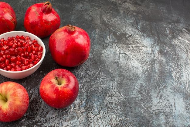 Visão de close-up lateral romãs maçãs romãs em torno de uma tigela de sementes de romã