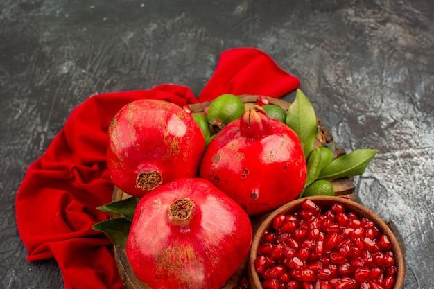 Visão de close-up lateral sementes de romã com folhas na mesa da cozinha