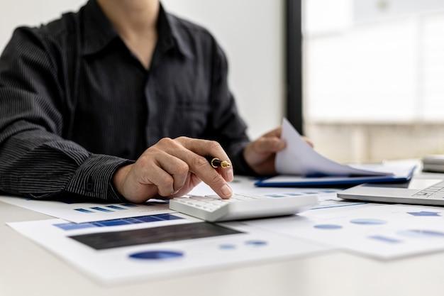 Visão de close-up um empresário usando uma calculadora para calcular números nos documentos financeiros de uma empresa, ele está analisando dados financeiros históricos para planejar como fazer a empresa crescer. conceito financeiro.