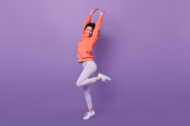 Visão de comprimento total da linda mulher asiática dançando com um sorriso. foto de estúdio da cativante modelo coreana em pé sobre uma perna.