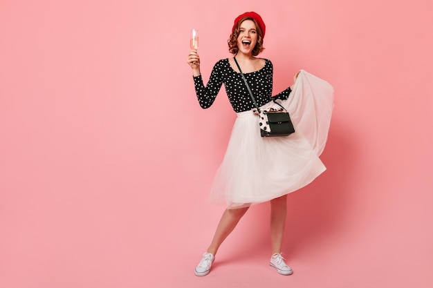 Visão de comprimento total de alegre garota francesa brincando com saia. mulher encaracolada feliz na boina segurando um copo de vinho no fundo rosa.