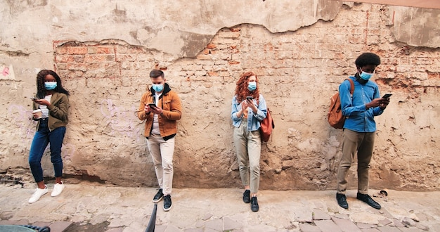 Visão de comprimento total de distanciamento social da empresa multirracial de pessoas usando máscaras de proteção ...