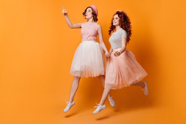 Visão de comprimento total de meninas correndo em saias. foto de estúdio de atraentes senhoras caucasianos, pulando sobre fundo amarelo.