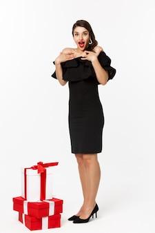 Visão de comprimento total de mulher em um vestido elegante e lábios vermelhos, parecendo surpresa, receber presentes nas férias de natal, em pé com presentes sobre fundo branco.
