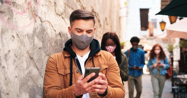 Visão de corpo inteiro da empresa multirracial de pessoas usando máscaras protetoras em pé com cada ...