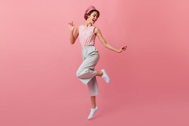 Visão de corpo inteiro da senhora dançando em calças
