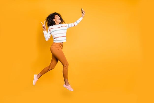 Visão de corpo inteiro de corpo inteiro de garota vestindo suéter, pule, tire uma selfie mostrando o sinal de v