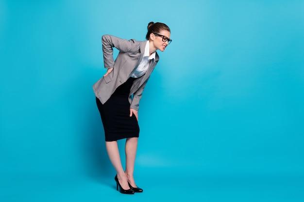 Visão de corpo inteiro de corpo inteiro de professora de negócios doente elegante se sentindo mal inclinada tocando costas doente isolado fundo de cor azul brilhante