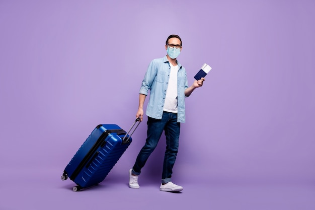 Visão de corpo inteiro de tamanho corporal de cara maduro segurando grande bilhete de bagagem chegue no exterior fazendo check-in usando máscara de segurança de gaze coberturas de prevenção 2019-ncov china wuhan isolado roxo violeta lilás cor de fundo