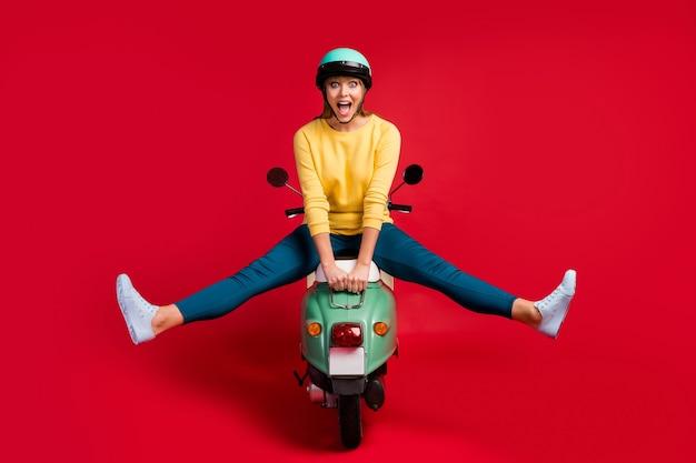 Visão de corpo inteiro de uma garota louca e descuidada sentada em uma motoneta