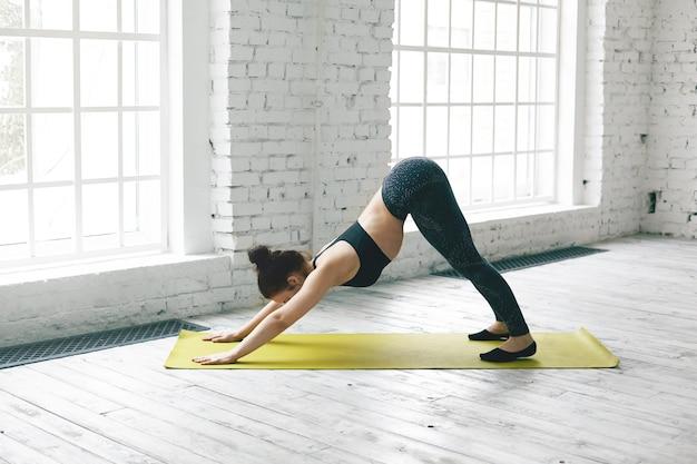 Visão de corpo inteiro de uma jovem flexível com corpo esguio, malhando na sala de ginástica, fazendo ioga, fazendo exercícios com tapete no chão de madeira, fazendo pose de cachorro virado para baixo ou adho mukha svanasana