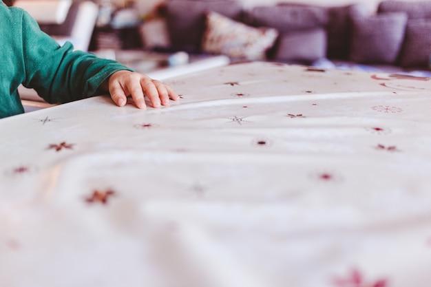 Visão de foco seletivo de uma mão minúscula em cima de uma mesa com um fundo desfocado