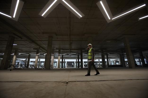 Visão de grande angular de um empresário maduro usando capacete de segurança e falando ao telefone enquanto caminha pelo canteiro de obras dentro