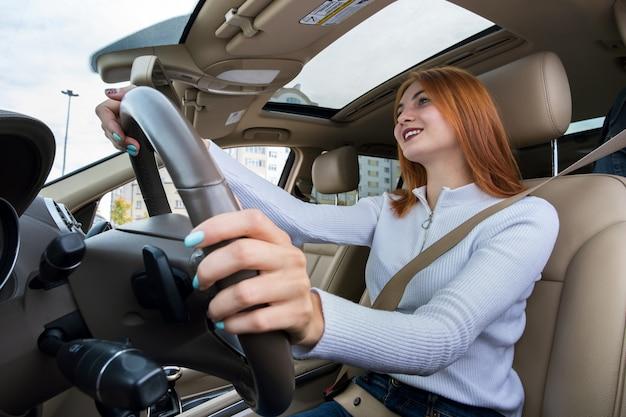 Visão de grande angular do motorista jovem ruiva prendida pelo cinto de segurança, dirigindo um carro sorrindo alegremente.