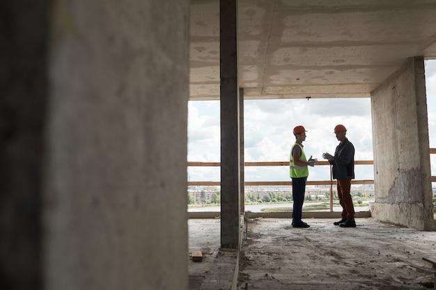 Visão de grande angular para dois trabalhadores discutindo engenharia no espaço de cópia do local de construção