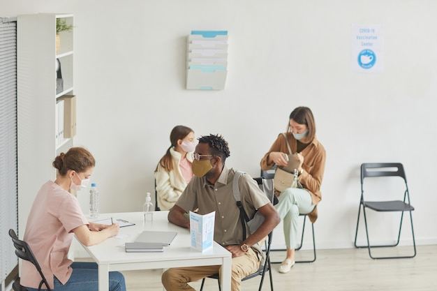 Visão de grande angular para enfermeira registrando pacientes que aguardam na fila do centro médico, copie o espaço