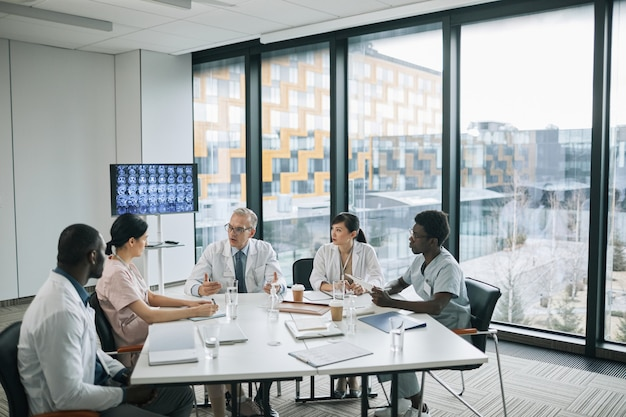 Visão de grande angular para médicos sentados à mesa de reunião na sala de conferências durante o conselho médico, copie o espaço