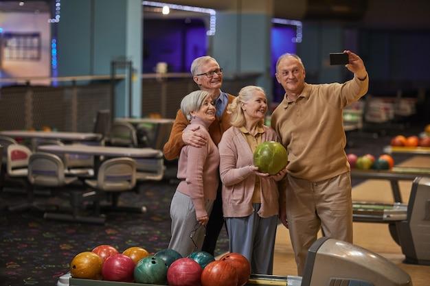 Visão de grande angular para um grupo de idosos tirando fotos de selfie jogando boliche e desfrutando de entretenimento ativo na pista de boliche, copie o espaço