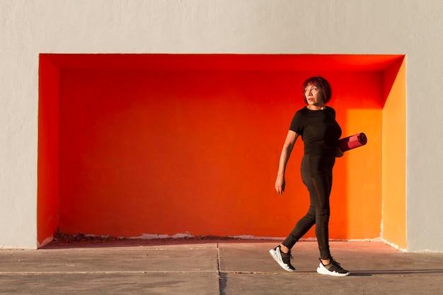 Visão de longo prazo de mulher segurando um tapete de fitness