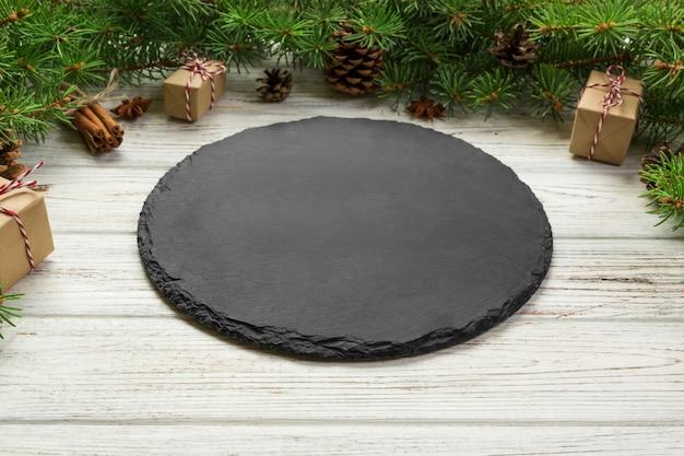 Visão de perspectiva. placa de ardósia preta vazia no fundo de madeira do natal. prato de jantar de férias com decoração de ano novo