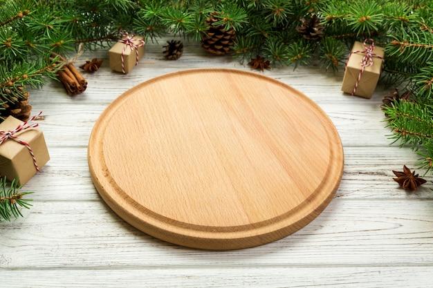 Visão de perspectiva. prato redondo de madeira vazio na placa de madeira do natal. conceito de prato de jantar de férias com decoração de ano novo