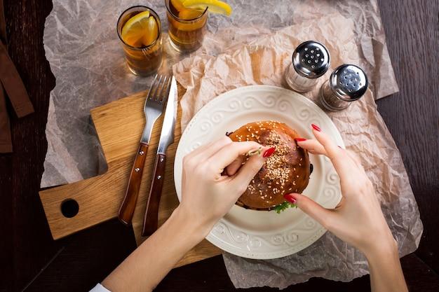 Visão de primeira pessoa de uma mulher se preparando comer hambúrguer. as mãos femininas seguram uma faca e um garfo. hambúrguer saboroso em um prato deitado