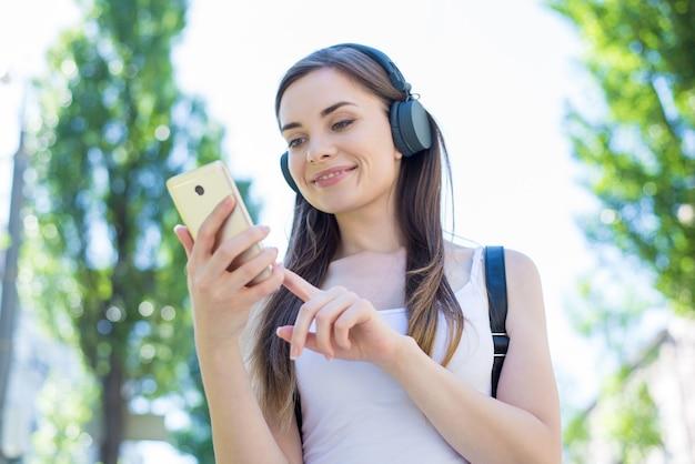Visão de retrato de foto de baixo ângulo de um usuário adorável e confiante segurando influenciador de telefone de dispositivo digital inteligente no instagram de rede segurando um telefone dourado tocando a tela sensível ao toque