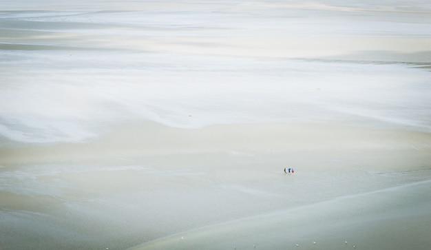 Visão de um grupo de turistas que andam na areia, no mudflat.