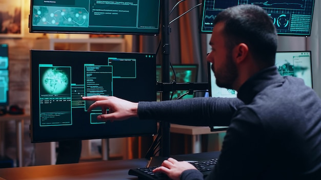 Visão de um hacker masculino codificando um vírus perigoso para atacar o banco de dados do governo. criminoso cibernético.