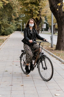 Visão de uma mulher usando máscara e andando de bicicleta