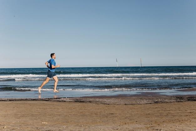 Visão distante do homem correndo na praia