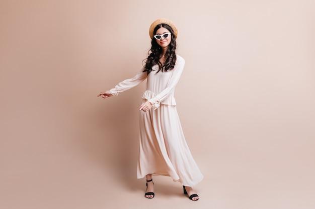 Visão do comprimento total da elegante mulher asiática no chapéu. foto de estúdio de moda mulher japonesa em pé sobre fundo bege.