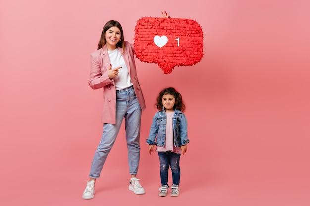 Visão do comprimento total da moderna mãe e filha posando com o ícone semelhante. foto de estúdio de família com símbolo de rede social.