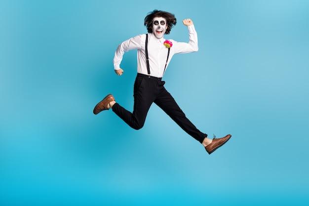Visão do tamanho total do corpo dele ele bonito funky alegre alegre ativo cavalheiro pulando se divertindo correndo movimento rápido calavera isolado brilhante vívido brilho vibrante fundo de cor azul