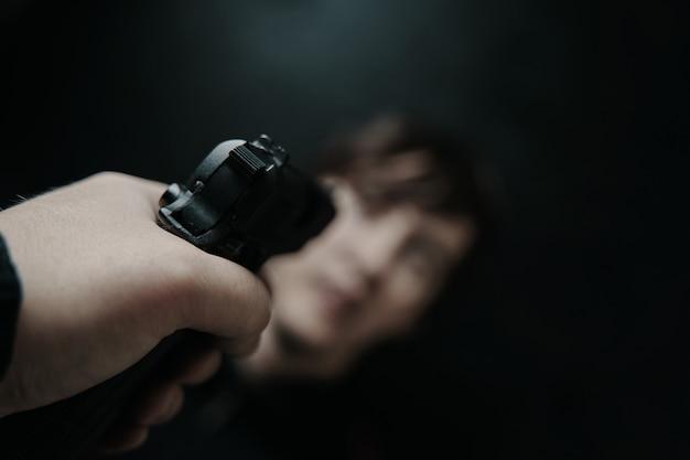 Visão em primeira pessoa de arma apontada para jovem em arma de fogo de fundo preto na mão do homem pov de apontar um ...